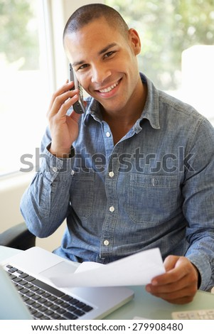 Young Man On Phone Using Laptop At Home - stock photo