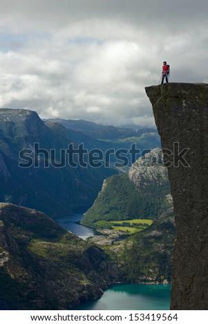 Young man on  preikestolen, kjerag, norway, extreme tourism - stock photo