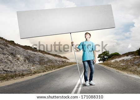 Young man on road holding blank banner. Place for text - stock photo