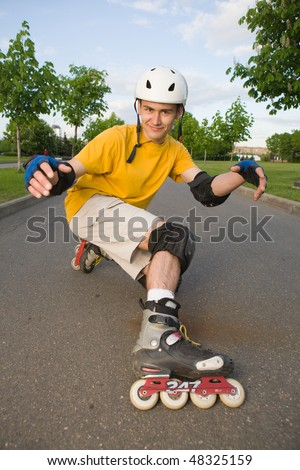 Young man on rollerblades at park - stock photo