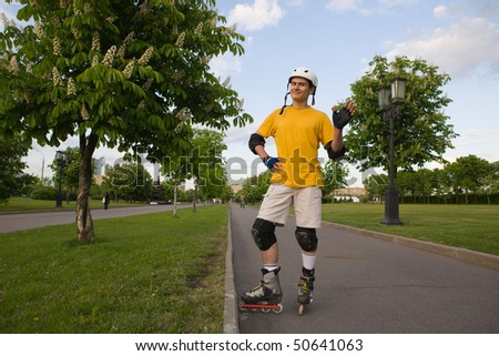 Young man on rollerblades standing at park