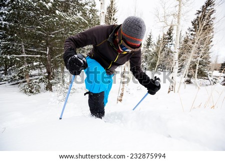 Young Man on Snowshoes Struggles to Get Up Snowbank  - stock photo