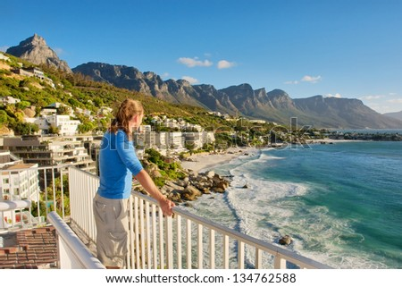 Young man on terrace looks at beach panorama. Shot in Cape Town, South Africa. - stock photo