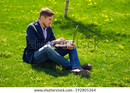 young man on the grass. fashion style. talking skype. outdoor