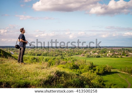 Young man on the grass hill with some photo equipment