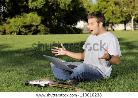 Young man on the grass with laptop