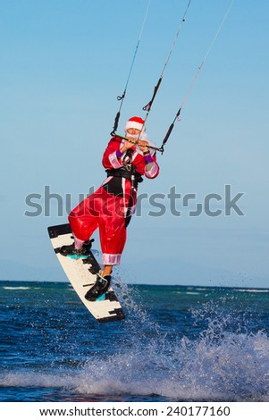young man on the kite in the costume of Santa Claus. Christmas and New year on a tropical island. Extreme Sport Kitesurfing - stock photo