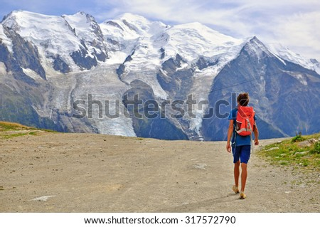 Young man on the mountain road, Alps on summer - stock photo