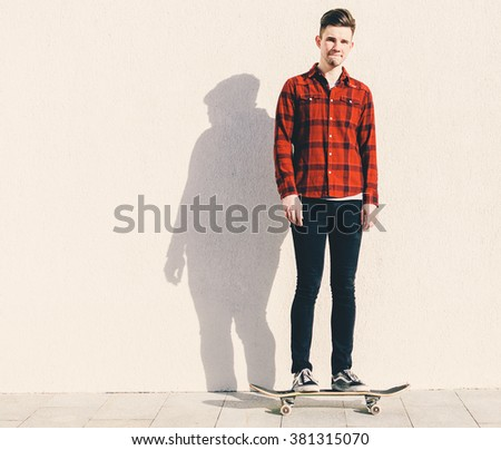 Young man on the skateboard on the city street - stock photo