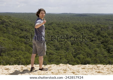 young man on the top of dune in pylat sur mer, france - stock photo