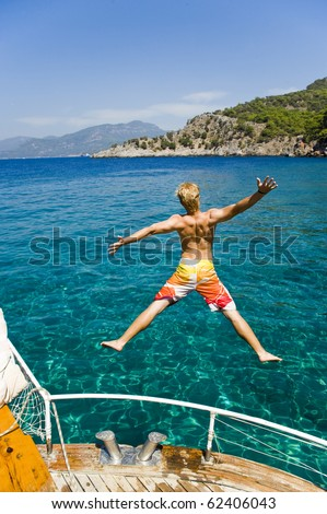 Young man on vacation jumping from a boat in turkey, enjoying his freedom, while on a summer holiday