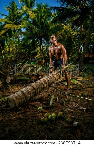 Young man on vacations training a palm tree