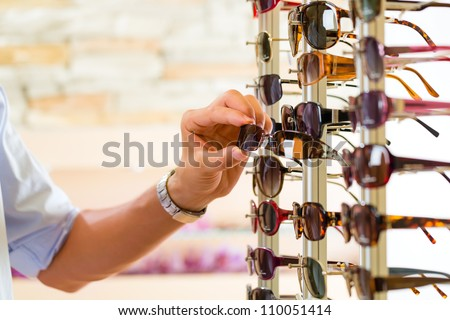 Young man (only hands) at optician with glasses, he might be customer or salesperson and is looking for sunglasses - stock photo
