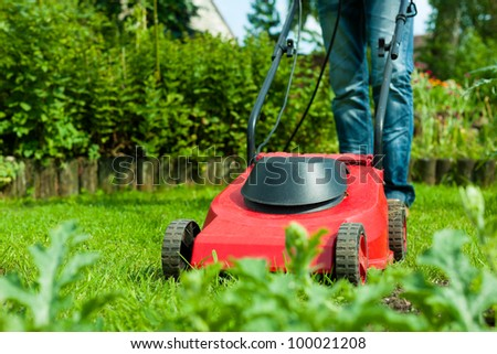 Young man - only legs to be seen - is mowing the lawn in summer with a mowing machine - stock photo