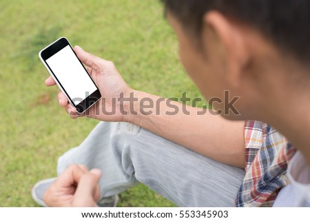 Young man or male hipster in casual wear sitting on green field  relax looking at blank screen mobile smart phone, close up.