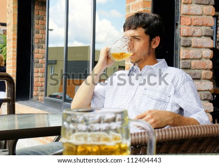 Young man or student drinking beer from glass bock while sitting outside at pub or restaurant terrace.
