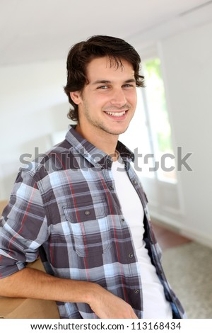 Young man packing boxes to move in new flat - stock photo