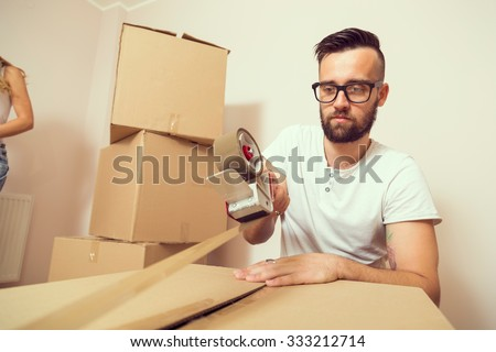 Young man packing things and taping boxes, preparing for moving out the apartment - stock photo