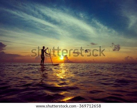 Young man paddle boarding during a beautiful sunrise in Mexico   - stock photo