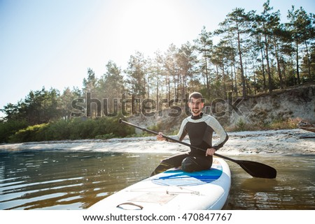 Young man paddling on sup board with paddle. Sitting pose - concept of harmony with the nature, free and healthy living, freelance, remote business.