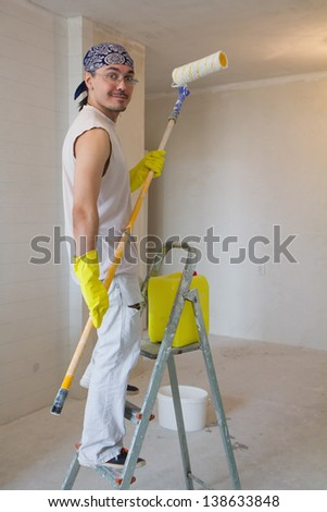 Young man painting ceiling with painting roller - stock photo