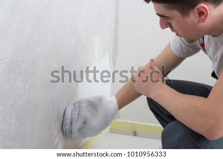 Young man painting grey wall. Home renovation concept