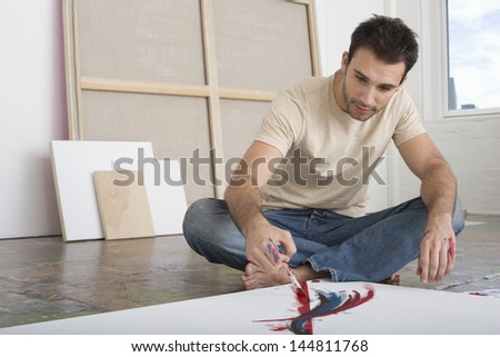 Young man painting on canvas on studio floor - stock photo