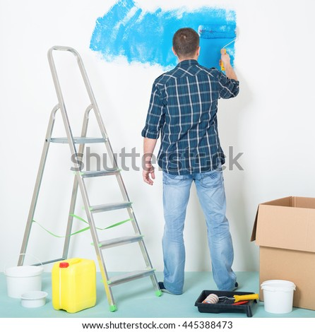 Young man painting wall at home - building and home concept