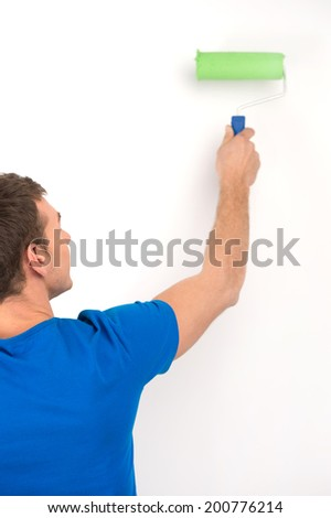 young man painting wall in green. back view of guy holding paint roller - stock photo