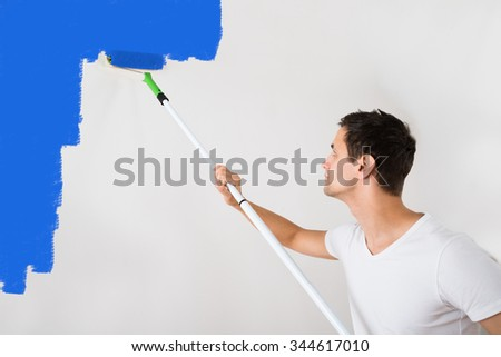 Young man painting wall with blue paint roller at home