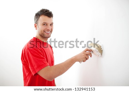 Young man painting wall with white paint.