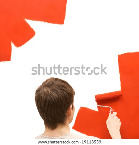 Young man paints the wall - stock photo