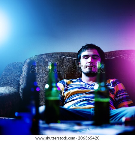 young man passed out drunk by himself - stock photo