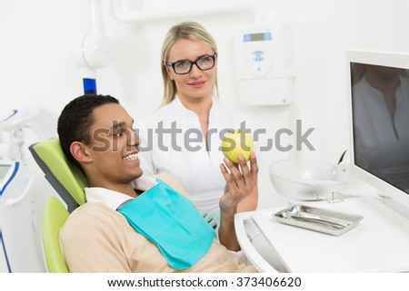 Young man patient smiling and looking at a green apple at dentist's office. Happy man got rid of his dental caries. - stock photo