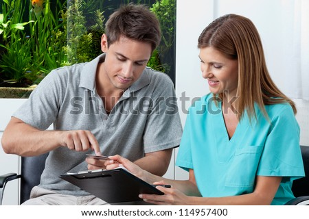 Young man paying bill through credit card to female dentist in clinic - stock photo