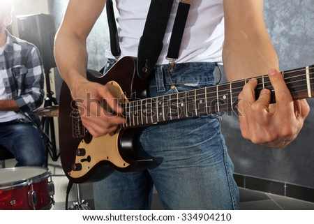Young man paying guitar closeup - stock photo