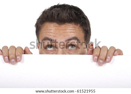 young man peeking behind empty white billboard - stock photo