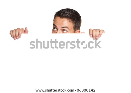 young man peeking behind empty white billboard