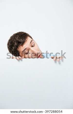 Young man peeking from blank board isolated on a white background - stock photo