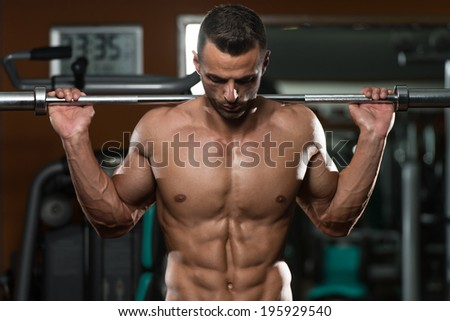 Young Man Performing Barbell Squats - One Of The Best Bodybuilding Exercise For Legs - stock photo