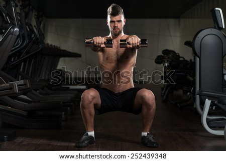 Young Man Performing Dumbbell Squats - One Of The Best Bodybuilding Exercise For Legs - stock photo