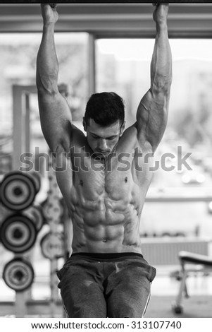 Young Man Performing Hanging Leg Raises Exercise - One Of The Most Effective Ab Exercises - stock photo
