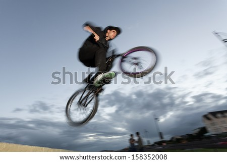 Young man performs BMX stunts during sunset at the street. Blurred motion.