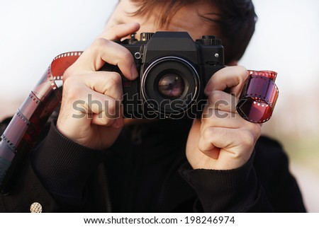 Young man photographer  holding vintage camera with film. outdoor Closeup portrait