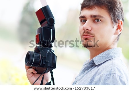 young man photographer with black professional camera and mobile flash