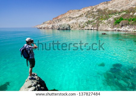 young man photographs the beautiful seascape camera - stock photo