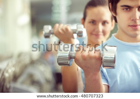 Young man picking up a dumbbell with woman on background