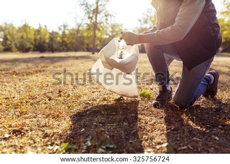 young man picking up trash outdoor. close up - stock photo