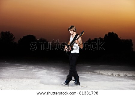 young man play electric guitar at sunset, full body shot
