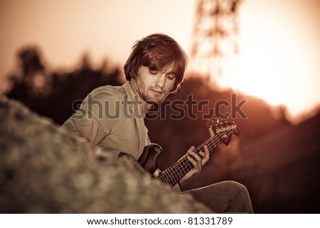 young man play guitar at sunset - stock photo